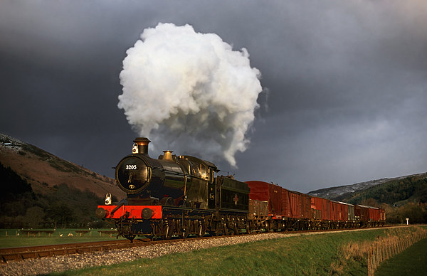 Goods train in the sun as a snowstorm approaches Canvas print by Ian Duffield