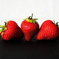 Buy canvas prints of Strawberries On White Over Black by Alan Harman