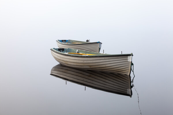 Boats reflected on a perfectly still loch. Print by Tommy Dickson
