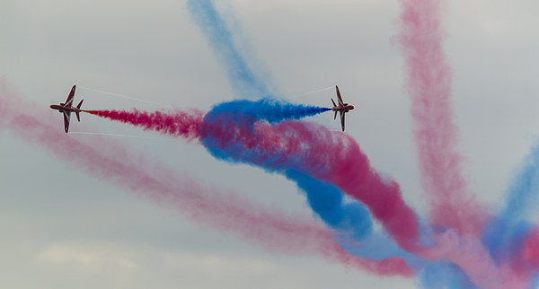 Two Red arrows crossing with smoke on Canvas print by Kenneth Dear