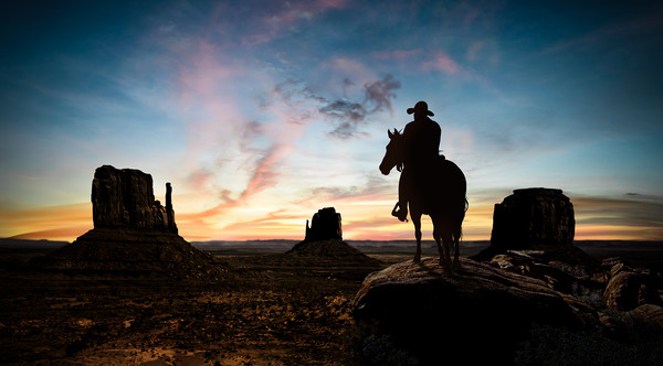 Silhouette of a cowboy at sunset Canvas print by Guido Parmiggiani
