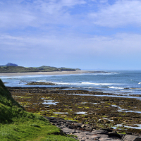Buy canvas prints of Bamburgh Castle From Seahouses by Tony Johnson