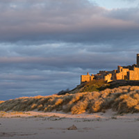 Buy canvas prints of Bamburgh Castle as the Sun goes down by Naylor's Photography
