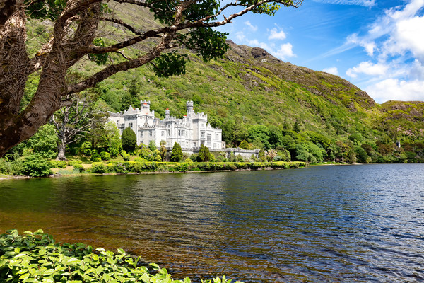 Kylemore Abbey in Connemara mountains with lake in Canvas Print by Thomas Baker
