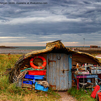 Buy canvas prints of Upturned boats used as fishing shelters - on Holy Island. by Richard Morgan