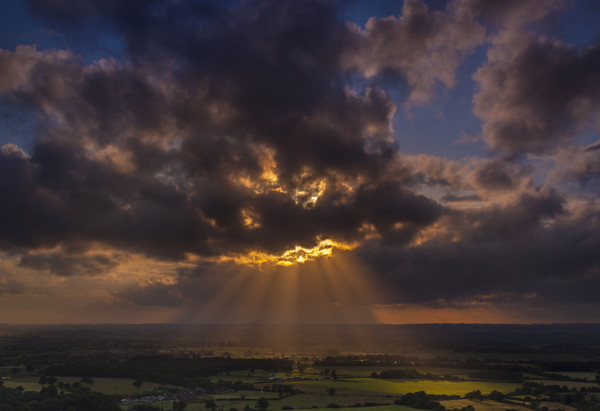 Crepuscular rays of sunlight shine onto fields in Dorset Canvas print by Alan Hill