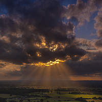 Buy canvas prints of Crepuscular rays of sunlight shine onto fields in Dorset by Alan Hill