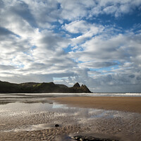 Buy canvas prints of Beautiful blue sky morning landscape over sandy Three Cliffs Bay by Matthew Gibson