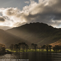 Buy canvas prints of Majestic vibrant Autumn Fall landscape Buttermere in Lake District with beautiful early morning sunlight playing across the hills and mountains by Matthew Gibson