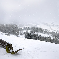 Buy canvas prints of Wooden bench on a hill and snowfall by Daniela-Simona Temneanu