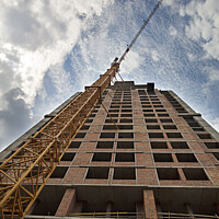 Buy canvas prints of New house under construction with a tower crane against the blue sky and birds in the sky by Sergii Petruk