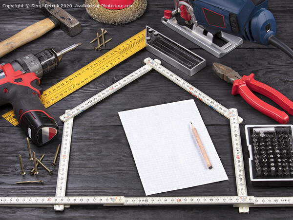 Tool for construction and repair on a black wooden background around a white sheet of paper with a pencil Framed Mounted Print by Sergii Petruk