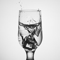 Buy canvas prints of An ice cube falls into a glass glass with water by Sergii Petruk