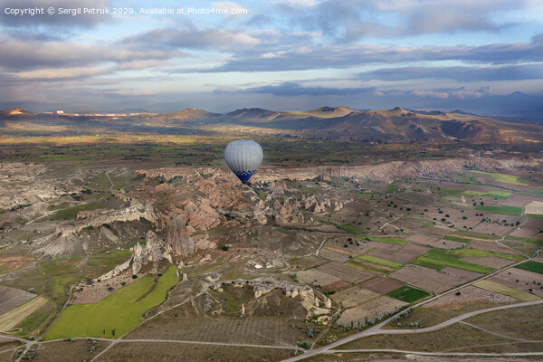 A balloons is flying over the valley in Cappadocia Print by Sergii Petruk