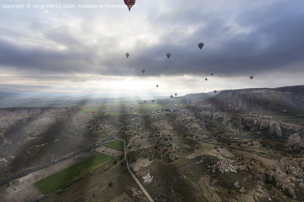 Balloons fly over the valleys in Cappadocia Print by Sergii Petruk