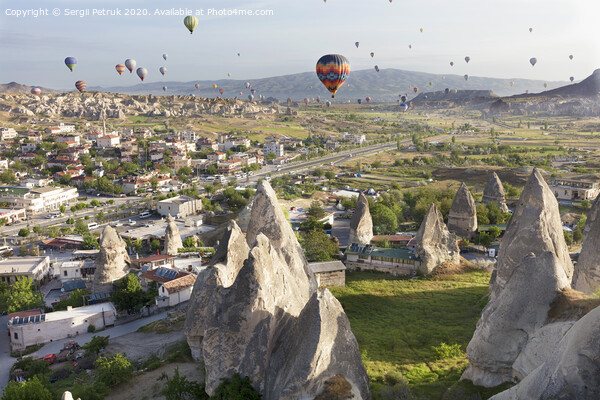 Dozens of balloons fly over the valleys in Cappadocia Print by Sergii Petruk