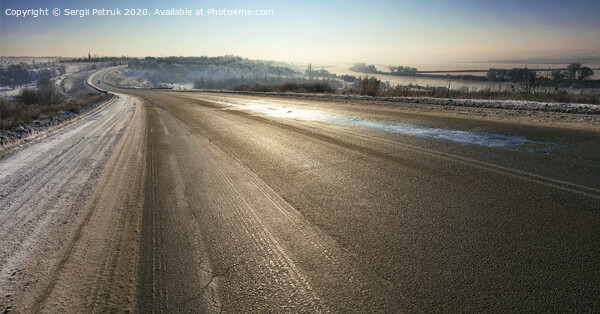 An old asphalt road is illuminated by sunshine in the winter morning. Print by Sergii Petruk