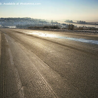 Buy canvas prints of An old asphalt road is illuminated by sunshine in the winter morning. by Sergii Petruk