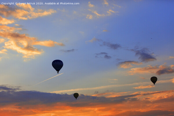 Silhouettes of balloons on the background of the morning sky with fiery red clouds. Canvas Print by Sergii Petruk