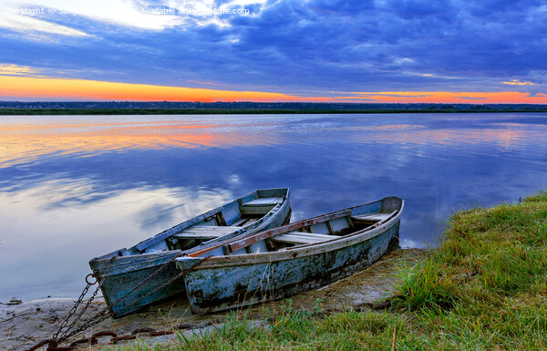 Two old blue-green boats moored by a metal chain to the shore of a calm river against the backdrop of the bright rising sun. Print by Sergii Petruk