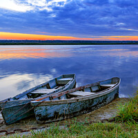 Buy canvas prints of Two old blue-green boats moored by a metal chain to the shore of a calm river against the backdrop of the bright rising sun. by Sergii Petruk