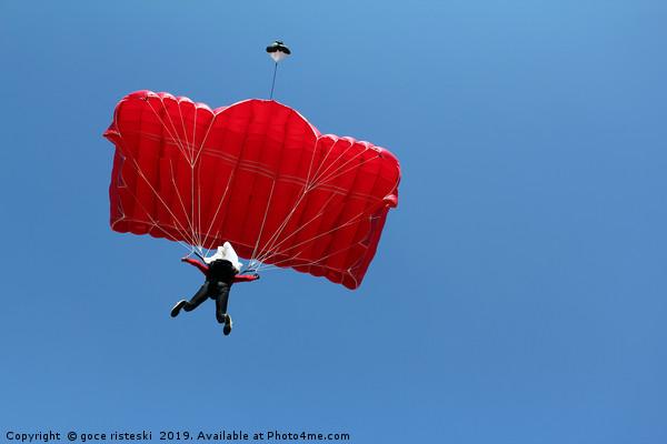 parachutist with red parachute on blue sky Canvas print by goce risteski
