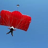 Buy canvas prints of parachutist with red parachute on blue sky by goce risteski