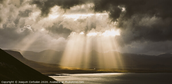Sunbeams fall among the clouds in a lake between mountains. Framed Print by Joaquin Corbalan