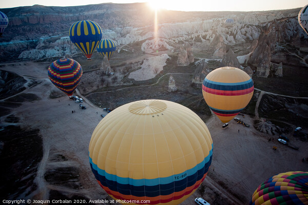 Hot air balloons for tourists flying over rock formations at sunrise in the valley of Cappadocia. Print by Joaquin Corbalan
