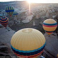 Buy canvas prints of Hot air balloons for tourists flying over rock formations at sunrise in the valley of Cappadocia. by Joaquin Corbalan