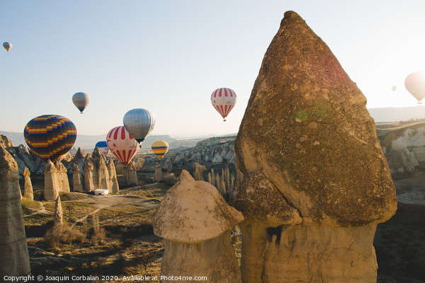 Goreme, Turkey - April 4, 2012: Hot air balloons for tourists flying over rock formations at sunrise in the valley of Cappadocia. Print by Joaquin Corbalan