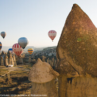 Buy canvas prints of Goreme, Turkey - April 4, 2012: Hot air balloons for tourists flying over rock formations at sunrise in the valley of Cappadocia. by Joaquin Corbalan