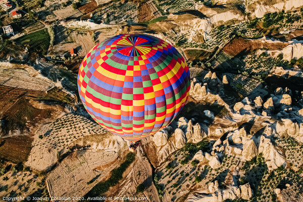 Travelers and tourists flying over mountains at sunset in a colorful aerostat balloon in Goreme, the Turkish cappadocia. Print by Joaquin Corbalan