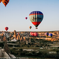 Buy canvas prints of Travelers and tourists flying over mountains at sunset in a colorful aerostat balloon in Goreme, the Turkish cappadocia. by Joaquin Corbalan