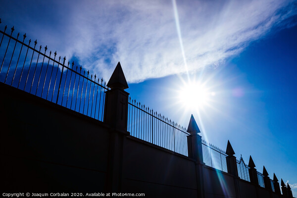 Silhouette against the sun of a high wall and metal fence with an intense blue sky in the background. Print by Joaquin Corbalan