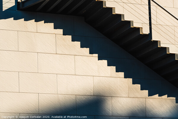 Minimalist wall with shadows from the upper steps of a modern stone staircase. Framed Print by Joaquin Corbalan