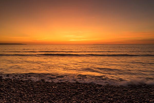 Waves on the sunset lit shoreline at Westward Ho Canvas Print by Tony Twyman