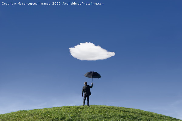 Businessman on a hill holding umbrella  Framed Mounted Print by conceptual images