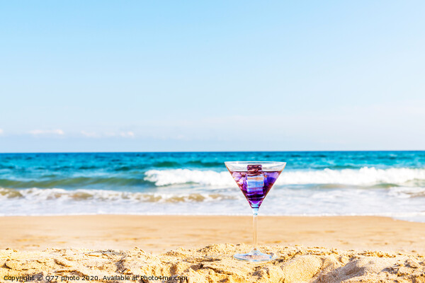 drink in a martini glass on the background of the waves affecting the sandy beach, relax on the beach, refreshing drink during the holidays Print by Q77 photo
