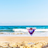 Buy canvas prints of drink in a martini glass on the background of the waves affecting the sandy beach, relax on the beach, refreshing drink during the holidays by Q77 photo