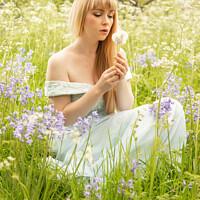 Buy canvas prints of Woman Blowing Dandelions by Amanda Elwell