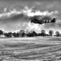 Buy canvas prints of Spitfire Fly Past - Mono  by J Biggadike