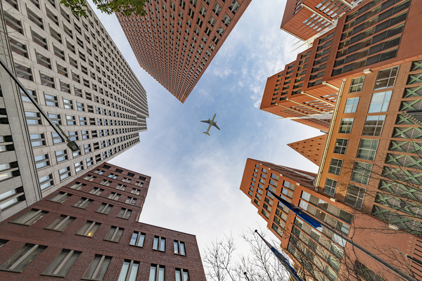 A plane flying over the headquarters and modern br Canvas print by Charlie Brown