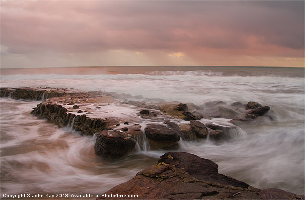 Rocks as the sea comes in Canvas print by John Kay