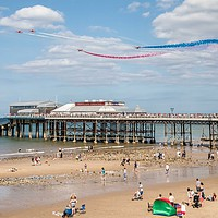 Buy canvas prints of Red Arrows Flying Over Cromer Pier  by David Woodcock