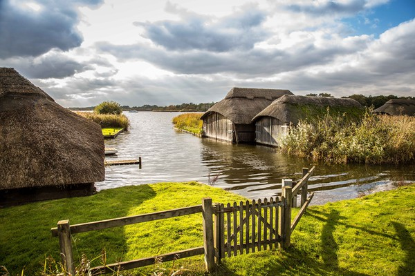Hickling Boathouses Print by David Woodcock